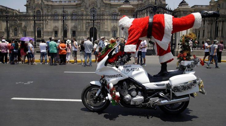El oficial de policía de tránsito Marco Chira, vestido con un traje de Santa Claus, realiza trucos en su motocicleta en movimiento fuera del palacio del gobierno en el centro de Lima, Perú, el martes 20 de diciembre de 2016. (AP / Martin Mejía)