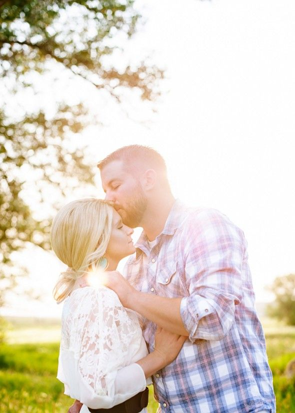 Outdoor Rustic Engagement Picture. Kissing on the forehead. Pretty lighting.