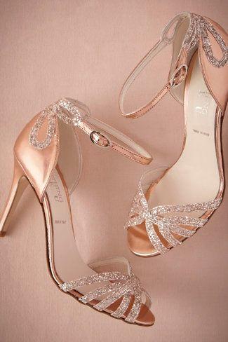 Pour terminer cette sélection de chaussures de mariées brillantes, on craque pour ces sandales de ce créateur de robes de mariées que l'on aime beaucoup. Le tissu est métallisé, d'une teinte rose doré. Les talons sont de 9 cm environ, mais la chaussure assure un bon maintien avec ses nombreuses brides. L'une d'elles, à la cheville, est ajustable. Par-dessus est cousu un joli nœud en strass. On retrouve ces brillants sur les brides croisées au bout du pied. De vraies chaussures de princesse…