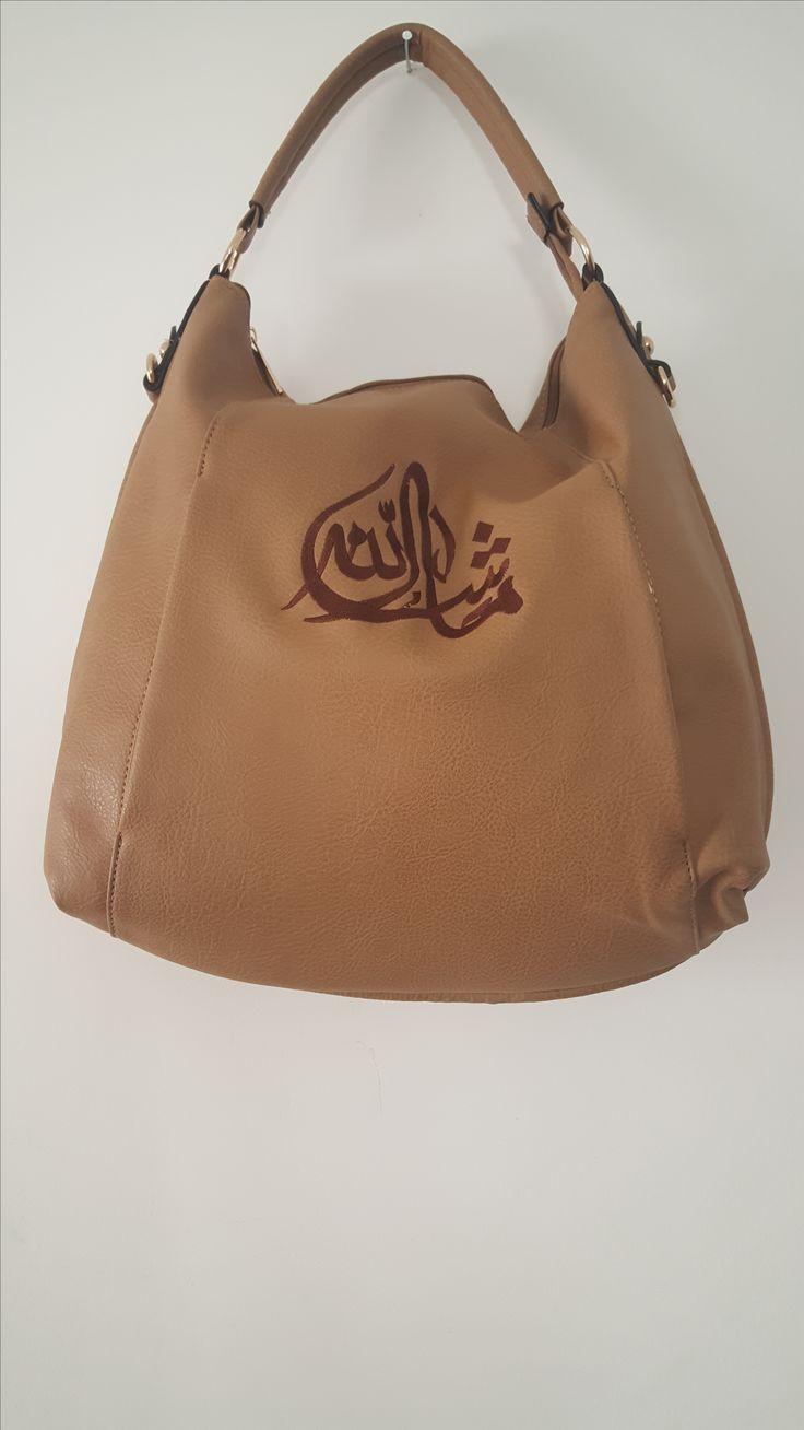 """Sac à main classique et moderne avec bandoulière et deux poches latérales et une poche arrière. Ce sac est confeccioné d'un cuir imitation de haute qualité, orné d'une calligraphie brodée """" Masha Allah """" qui vous procure un effet d'élégance.Indispensable pour le travail ce vaste sac souple offre suffisamment de place pour acueillir une tablette , un porte feuille et bien plus encore."""