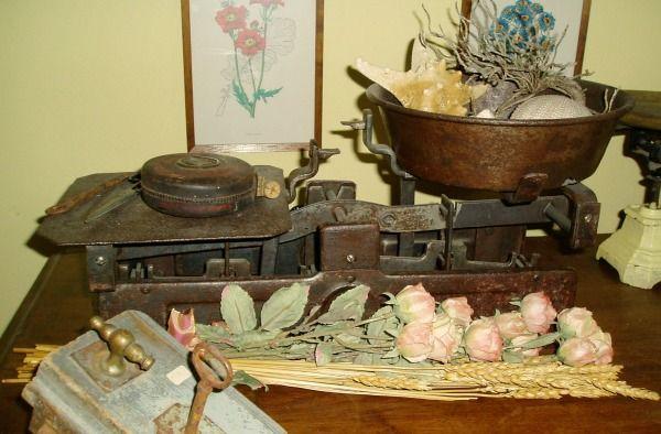 Una vecchia bilancia, una toppa antica e dei fiori di seta, un insieme country da sistemare su un tavolino o su un piccolo cassettone.