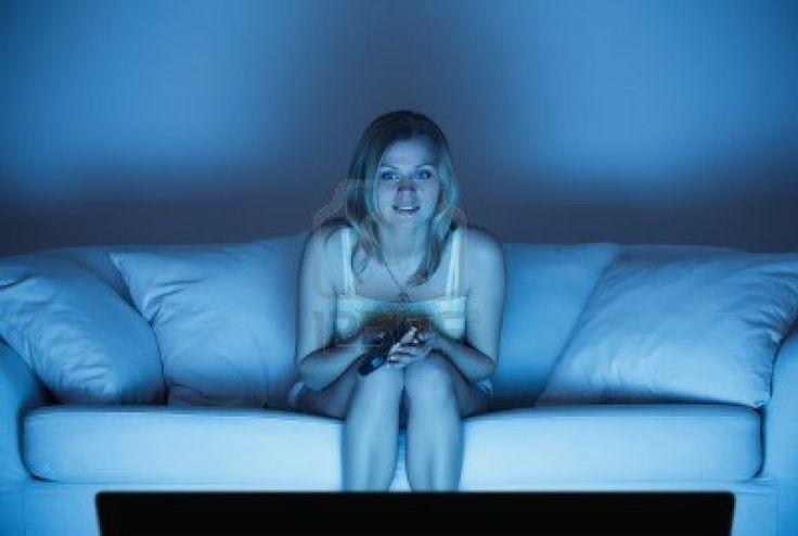 mooie eenzame vrouw zit op de bank en tv kijken Stockfoto - 9654434