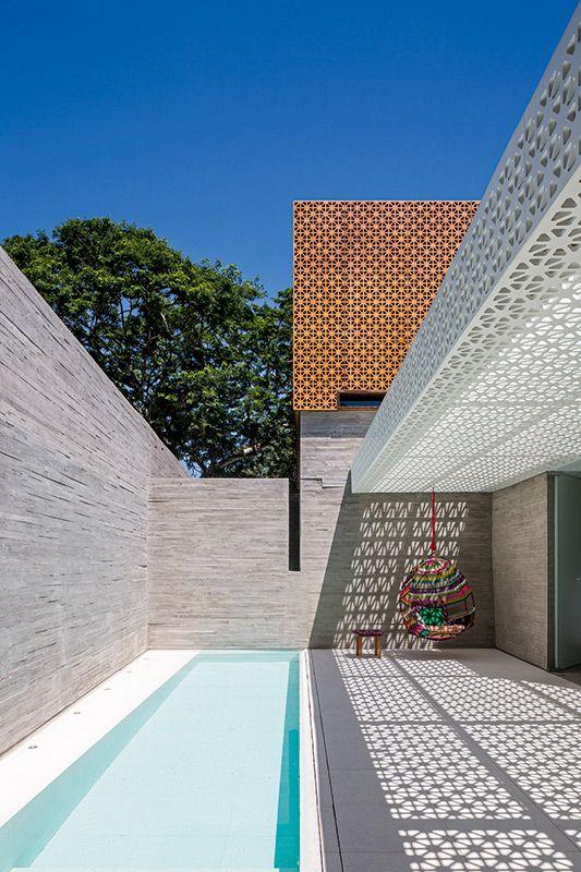 O pátio maior, aberto para o alto, é ocupado pela longa piscina e por área de relaxamento protegida por teto em pérgula, que tem desenho  de muxarabi