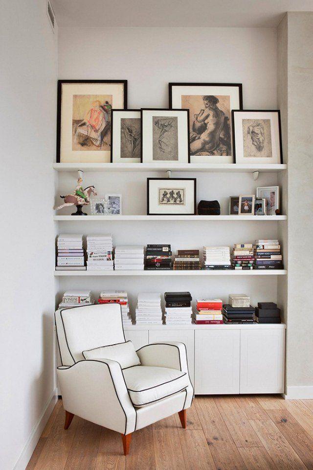 une bibliothèqye blanche et épurée décorée de tableaux et photos