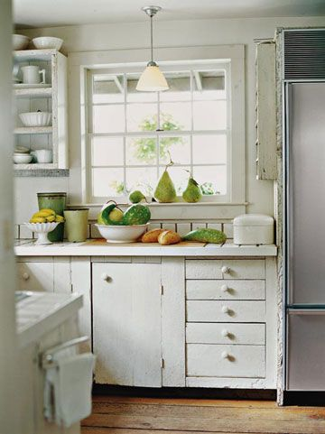 Create a Cottage Kitchen - install a wood or tile floor.  Hardwood floor finished with polyurethane is easy to maintain.  Hide recessed lighting.  Eliminate clutter, make space for appliances in cupboards rather than countertops, put staples like flour, sugar in simple glass containers, add a vintage piece of storage furniture.