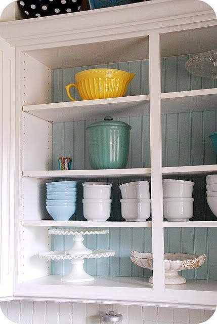 Oh, smart!  Just remove 2 kitchen cabinet doors, add painted beadboard in back.  Voila, adorable open-shelving decor focal point!