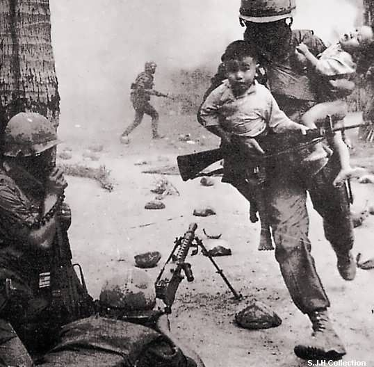 This image shows an American soldier risking his life to save two Vietnamese children during a fight.  This is bravery.  A man risking his life to save the enemy's children  #OneBraveThing