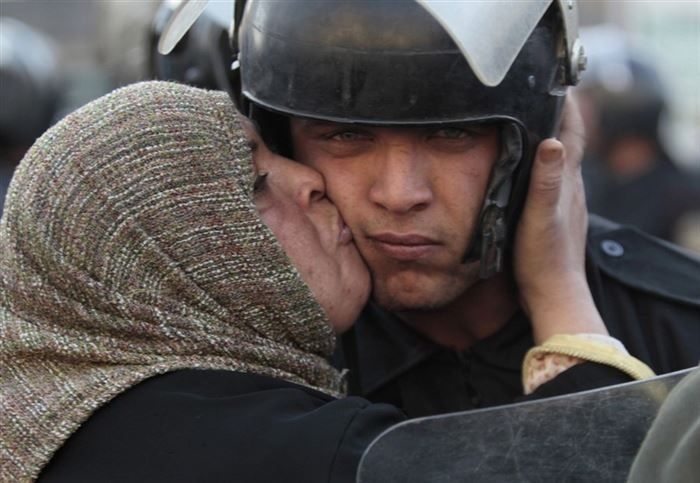Egyptian woman kisses an officer during riots.