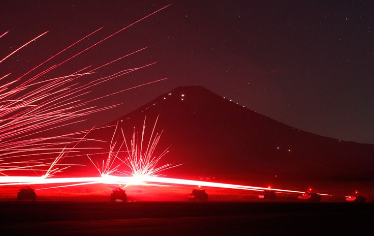 Tracer bullets ricochet off their targets as Japanese Ground Self-Defence Force Type 74 and Type 90 armored tanks fire machine guns during a night training session at Higashifuji training field in Gotemba, west of Tokyo, on August 21, 2012. Mt. Fuji stands in the background. (Reuters/Issei Kato) #