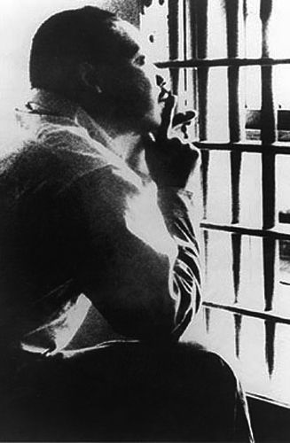 """Rev. Dr. Martin Luther King, Jr., in jail in Birmingham, Alabama, April 1963.  In response to criticisms from local clergy that a man of the cloth should not encourage his followers to break the law, King famously penned his """"Letter from a Birmingham Jail"""" from this cell."""