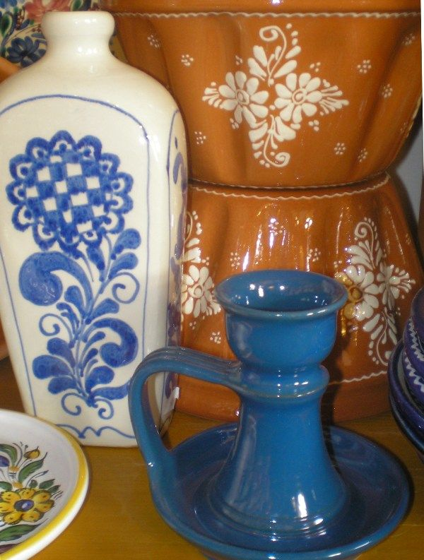 Hungarian traditional ceramics: a bottle for brandy, a baking form for cakes and a blue candelabra. They are all fully handmade.