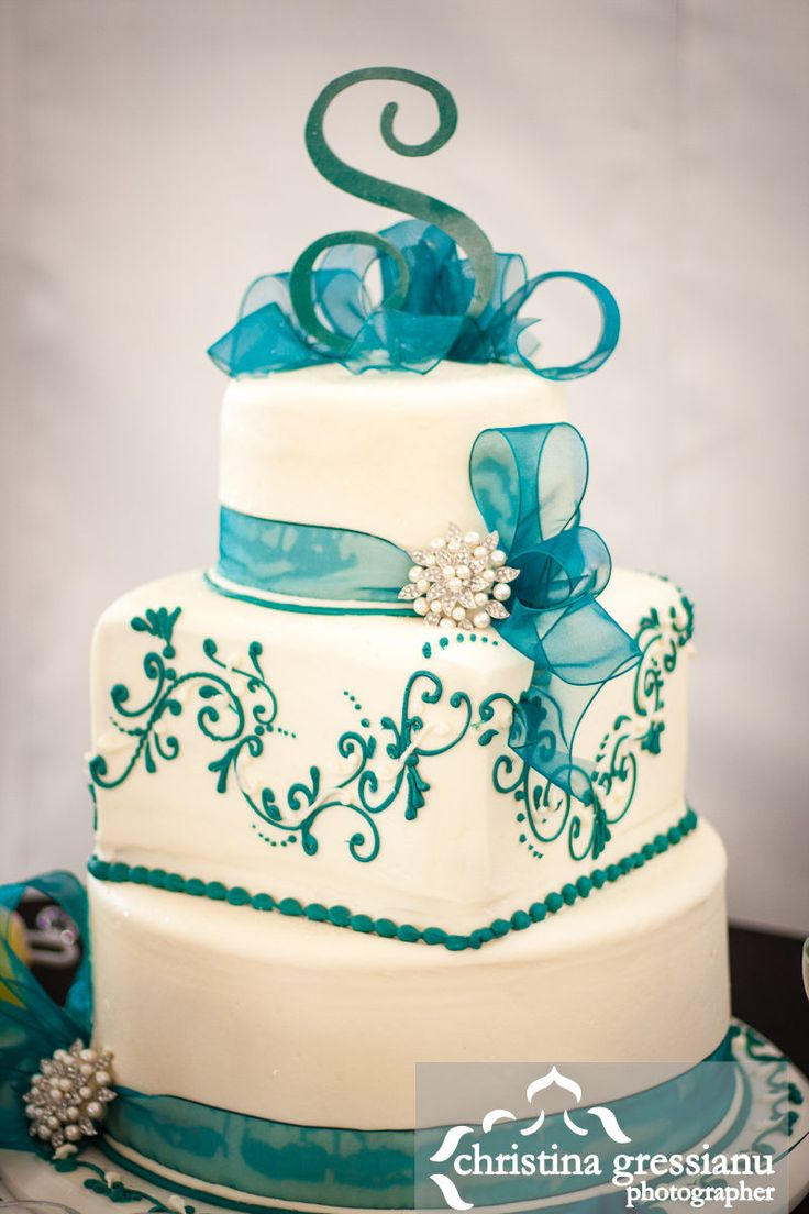 A Pretty White And Teal Wedding Cake With A Brooch Accent.