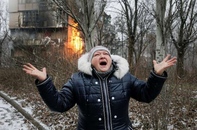 A woman reacts as the residential block in which she lives in burns — a result of recent shelling, a... - Maxim Shemetov/Reuters