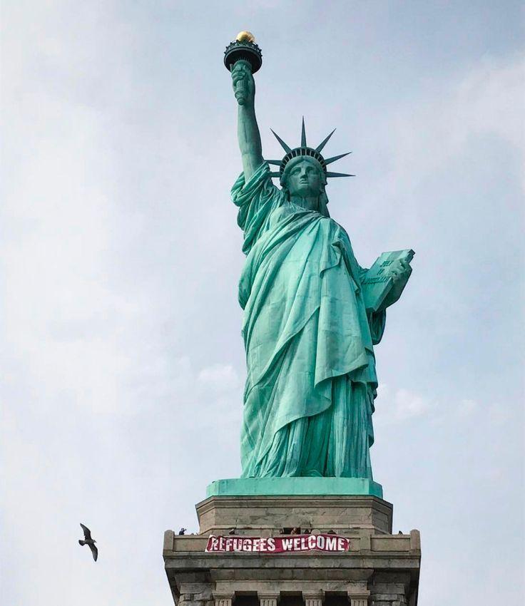 Статуя Свободы сплакатом «Беженцы, добро пожаловать». Фотография — Meduza