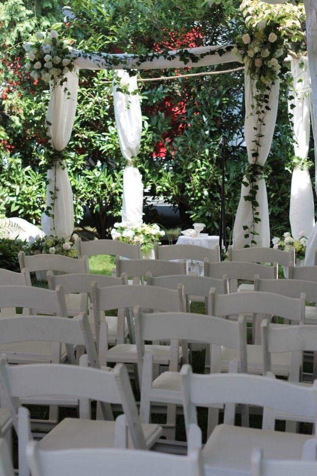 A backyard chuppah with flowers and birch tree poles