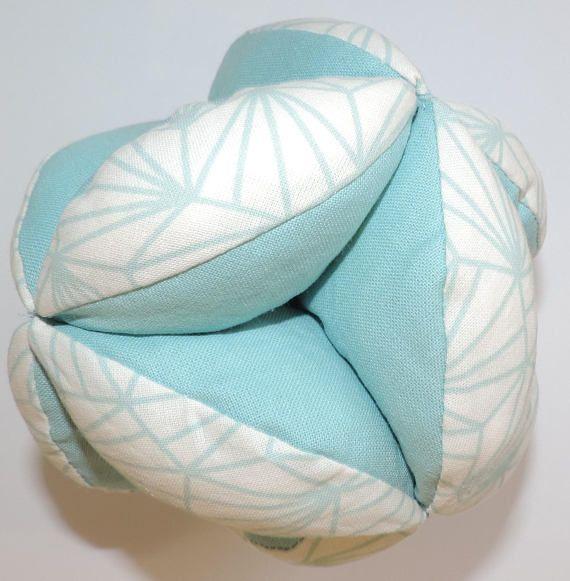 Balle de préhension Montessori Tissu en coton vert deau et tissu en coton avec des motifs dorigami vert deau sur fond ivoire. La balle est remplie en rembourrage anti acarien, ce qui est adapté aux enfants en bas âge. Cette balle de préhension permettra léveil de votre enfant. Il sagit dun jeu éducatif composé de 12 parties assemblées. Le fait que la balle soit rembourrée permettra à votre enfant dattraper facilement la balle. Dimensions : - Diamètre : environ 12 cm Vous pouvez égalemen...