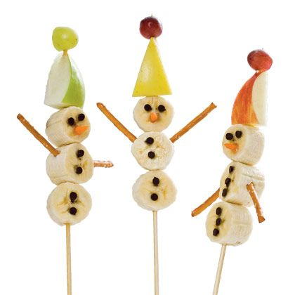 For each snowman, you will need three thick slices of banana, a grape, a sliver of carrot, and a triangular piece of apple. (Tip: Poke a hole in the apple piece with a bamboo skewer first to make assembly easier.)  Have your kids slide the fruit onto the skewer, then use the carrot slivers for noses, mini chocolate chips for eyes and buttons, and pretzel sticks for arms.
