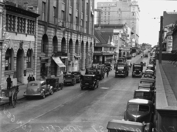 Traffic congestion on Elizabeth Street, Brisbane, 1939 - Parked cars line Elizabeth Street, while other cars, pedestrians and cyclists navigate the road.