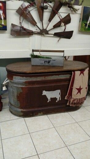 Old rusty water trough, repurposed into storage trunk/coffee table with hinged wooden lid. - By Redeemed Furniture & Decor, Talihina OK