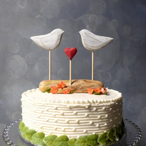 This listing is for a rustic, hand carved, wooden cake topper in weathered, natural tones. The hand carved love birds stand perched above a 5 piece of real driftwood. Between them is a carved wooden heart that has been burnished with fire, (for passion!) and finished in the rustic