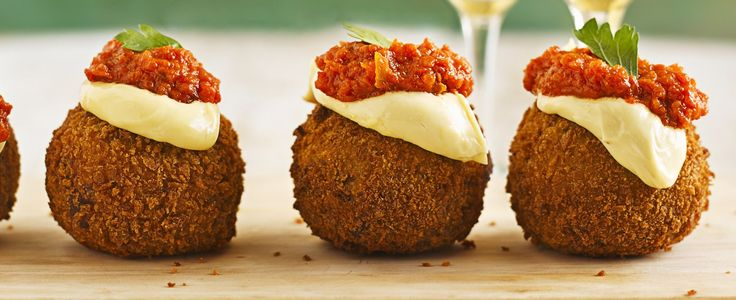 The best canapé using mashed potato. Pork mince wrapped in mash makes an easy nibble that's coated in breadcrumbs and served with spicy tomato sauce and aïoli.