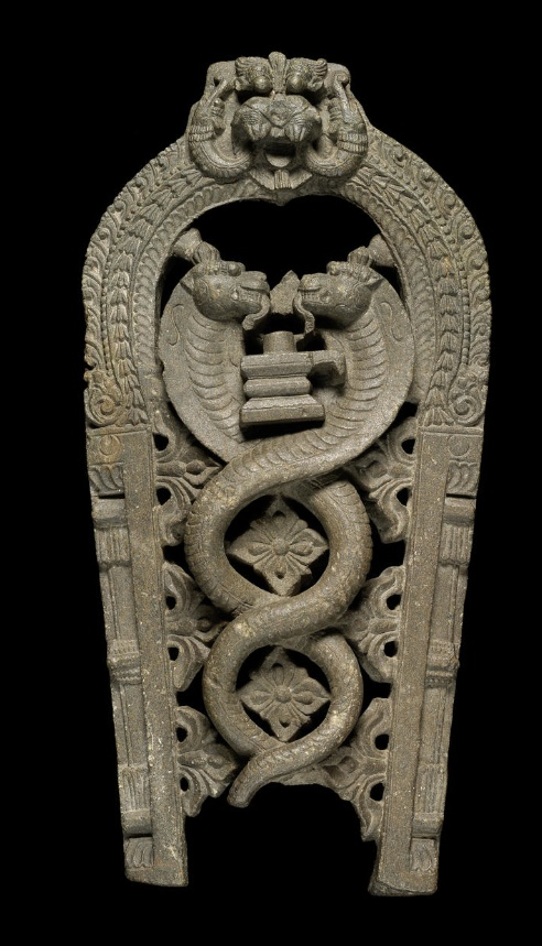 A carved stone Stele depicting Siva with two cobras   South India, 17th-18th Century  of arched form tapering towards either side at base and peaking with a makara head, the central area with two intertwining cobras, three trefoils either side and flower heads to interstices, their heads confronting either side of a lingam   64 cm. high x 31 cm. diam.