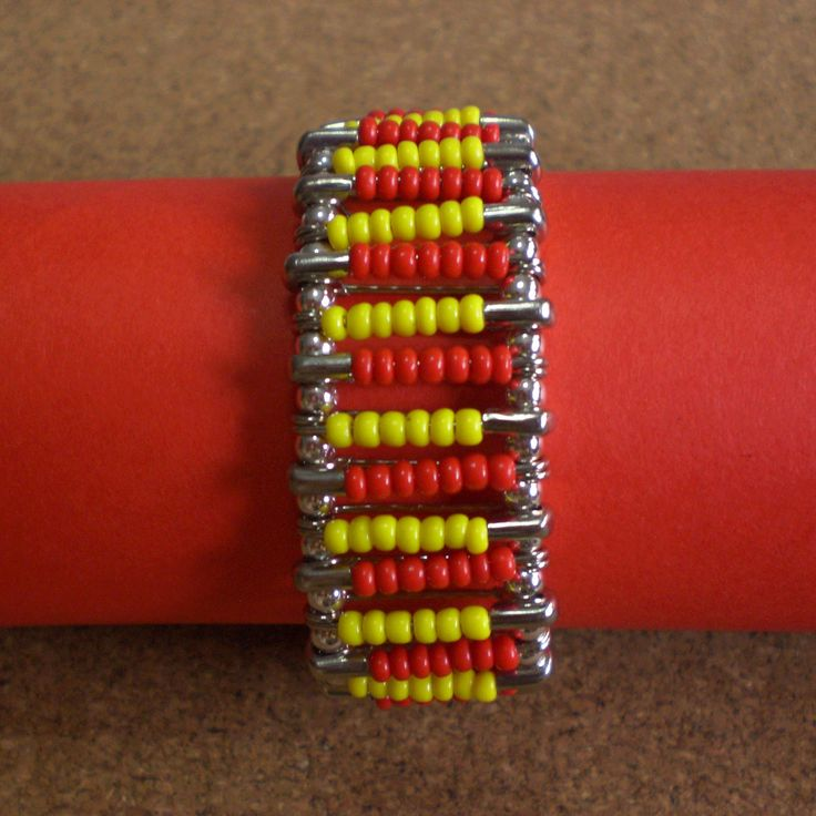 Bracelet made using safety pins with yellow and red plastic beads. Connected with silver round beads.