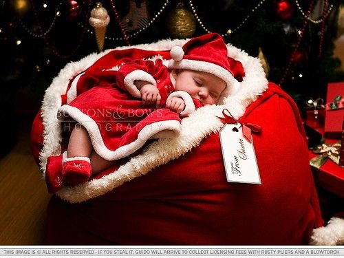 Baby poser wrapped in large red santa bag. we could make the tag and tie it on, and cover the inside of the bag and top of the baby poser with the blanket.
