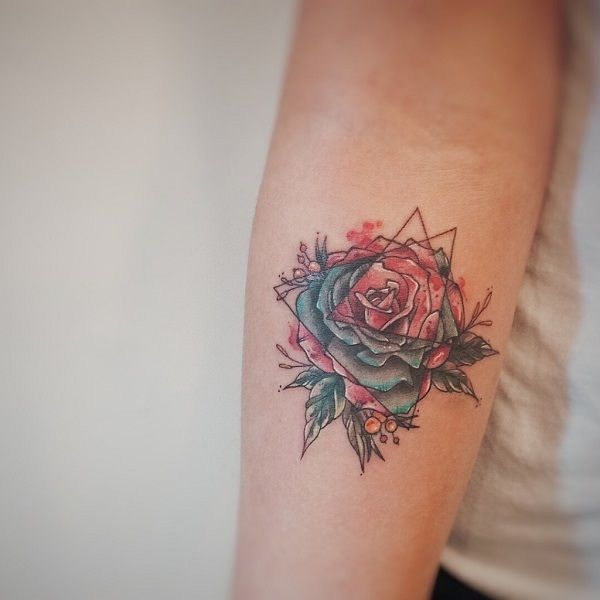 Double Triangle Glyph Tattoo design on the arm. The two triangle symbols are seen overlapping each other and have different colors within them. There is the red and the blue shade which highlight different parts of the flower.