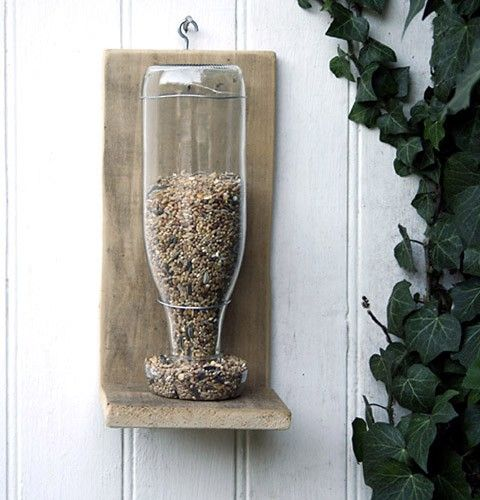 wood + wire + bottle+ birdseed = cute bird feeder; looks easy to make. i love the simple beauty.