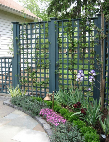 Vertical panels in a square lattice pattern protect a side yard from view. Love the beefy posts and lathing as well as the dark teal stain, making this solution people and plant friendly. For those within this space, it's nice to glimpse neighborhood activity on the sidewalk or street without feeling exposed.