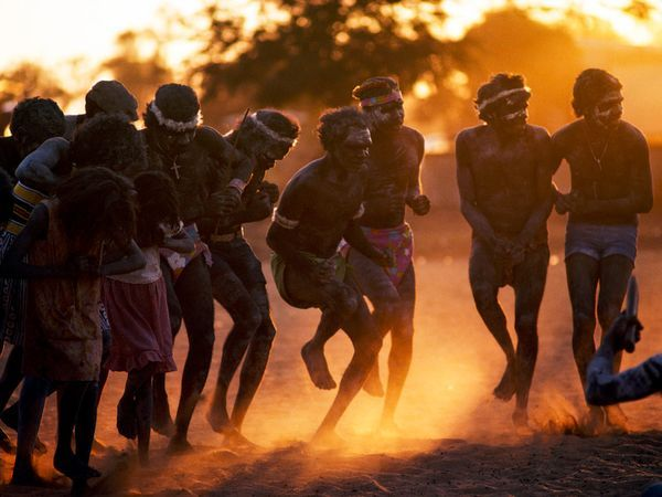 Photograph by Penny Tweedie/Getty Images - Aborigines kick up dust in a dance at sunset. The original inhabitants of Australia, Aborigines were there for more than 40,000 years before white men arrived. European settlers brought disease and politics to the continent, severely endangering the Aborigines' distinct culture, language, and lifestyle.