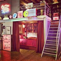 Cool bed with curtains for privacy and a desk space on top with stairs going up. Would do barn doors instead of curtains...
