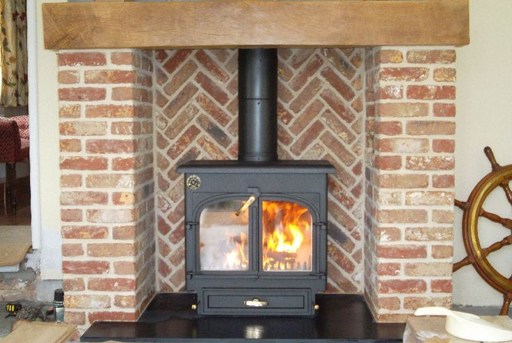 Clearview 650 multifuel stove in a brick herringbone fireplace.