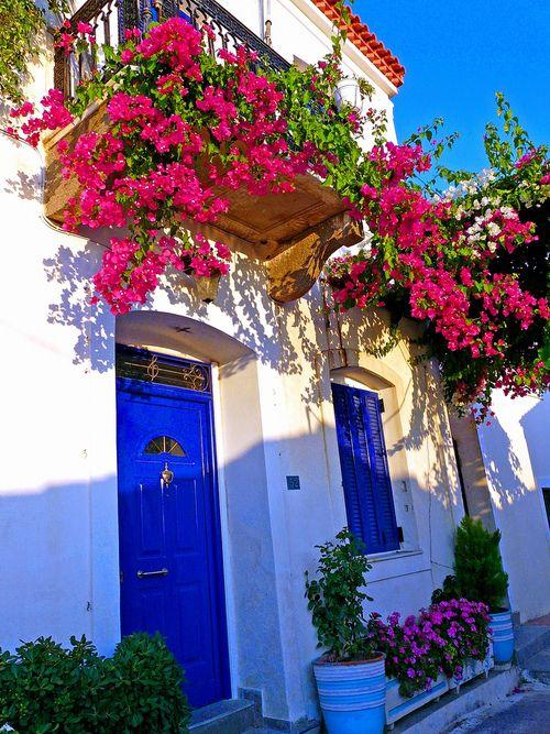 Balcony and bougainvillea Facade with flowered balcony. Poros island, Saronic, Greece