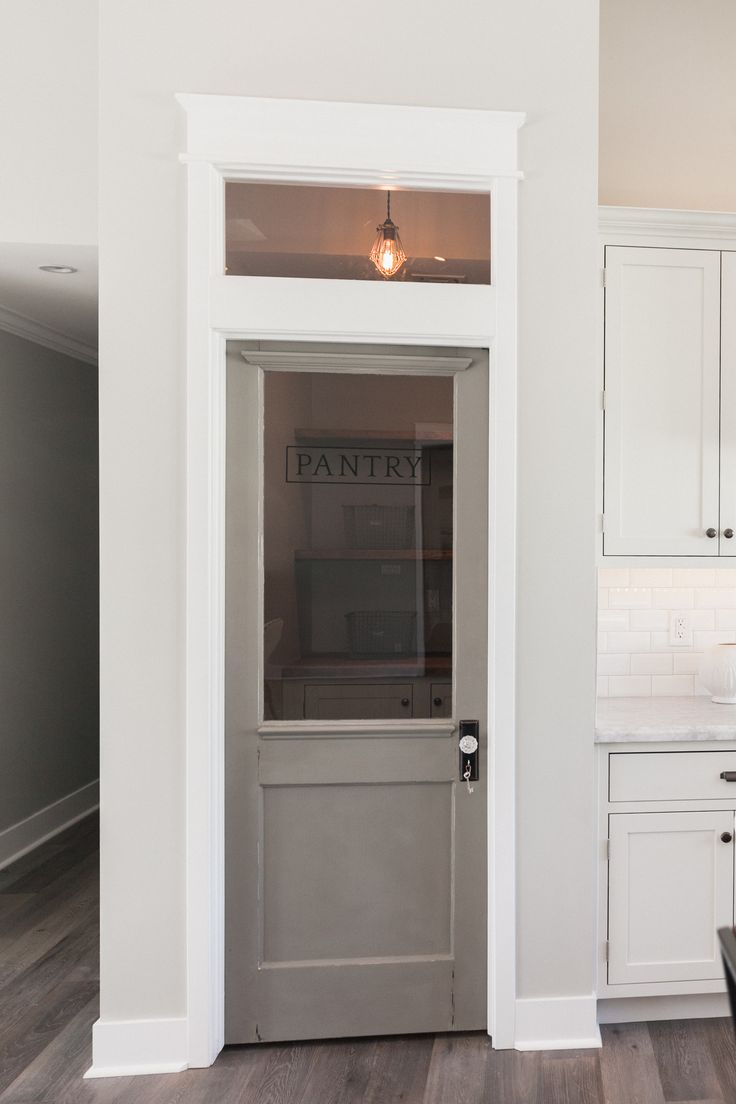 pantry door + transom window.  Love the white woodwork, gray door, and crystal door knob.