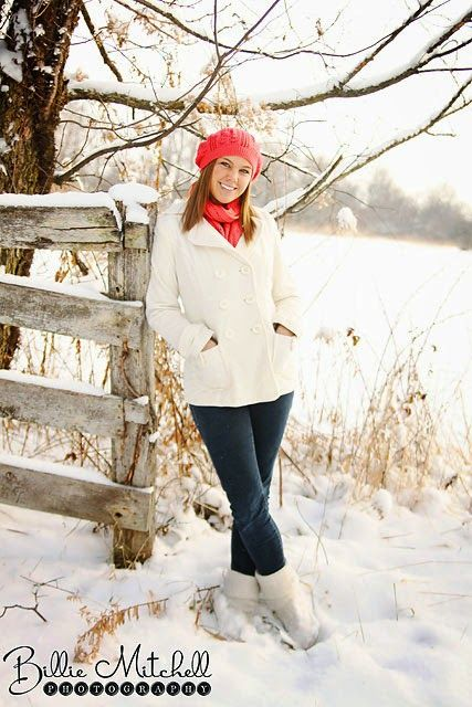 senior girl standing against snow covered fence wearing white wool jacket and orange hat and scarf