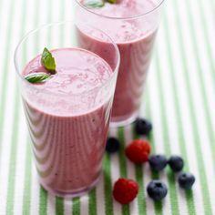 Mix de vruchten, het sinaasappelsap, de yoghurt en siroop in een keukenmachine. Garneer met basilicumblaadjes.