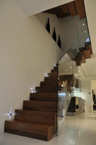 Dark wood stairs w/ glass handrail or guard rail