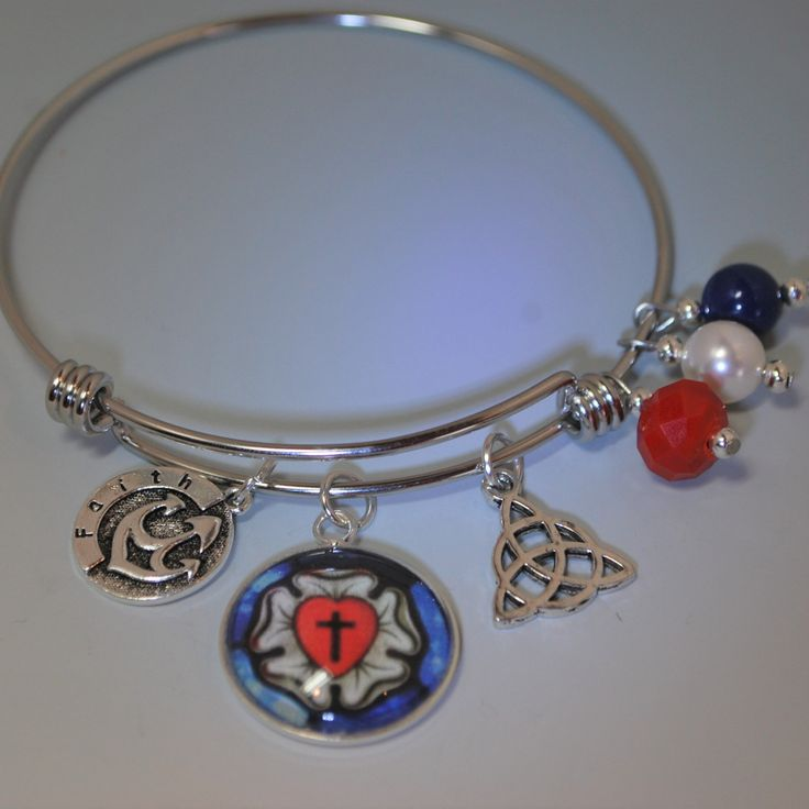 A custom Luther's Rose cabochon is at the center of this modern, expandable, bangle. This bracelet is made of non-tarnishing stainless steel and accented with Swarovski pearls and a brilliant red, fac