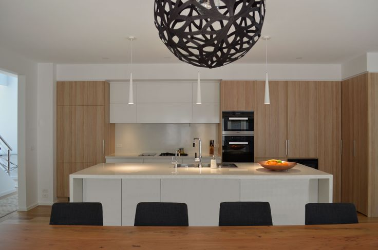 SUSIE MILES DESIGN Feature black pendant by David Trubridge over clients dining table, combined with slim white pendants above the kitchen island.