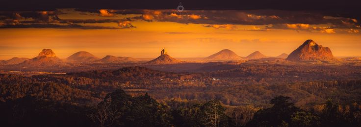 A short exposure, panoramic, landscape image of the Glass House Mountains in Queensland, Australia, at sunset.