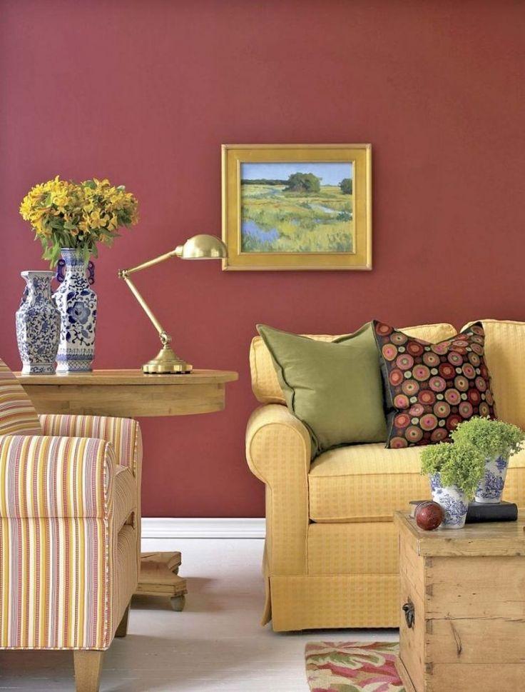 peinture rose, canapé en tissu jaune, fauteuil multicolore rayé et coussins décoratifs assortis