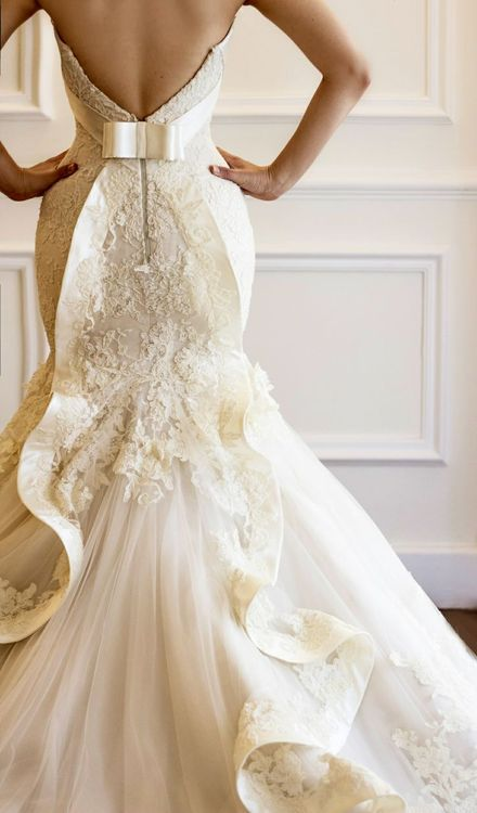stunning fit and flare wedding dress. covered in lace with tulle skirt, complete with bow detail