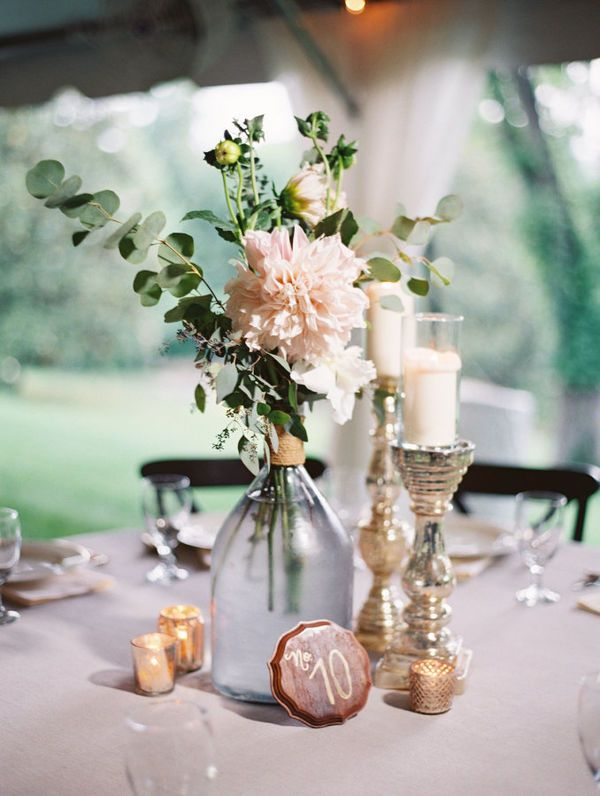 Garden Wedding Centerpiece Inspiration | Dahlias are perfect for your garden wedding. Place your wedding flowers inside a unique glass bottle and accompany with varied candlesticks and votive candles.