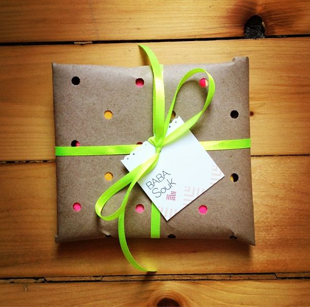 punch holes in brown craft paper and show birthday or Christmas gift wrapping underneath: