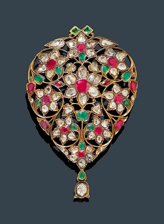 DIAMOND, RUBY AND EMERALD PENDANT, probably India ca. 1920. Pink gold. Very attractive, drop-shaped, florally open-worked pendant, set with 15 Burma rubies weighing ca. 1.00 ct, 14 emeralds and 55 rose-cut diamonds in different shapes weighing ca. 2.00 ct. The lower part with 1 bellflower, set with 1 oval rose-cut diamond of ca. 0.10 ct. On the back, fine florally engraved, closed settings. by Koller Auctions.