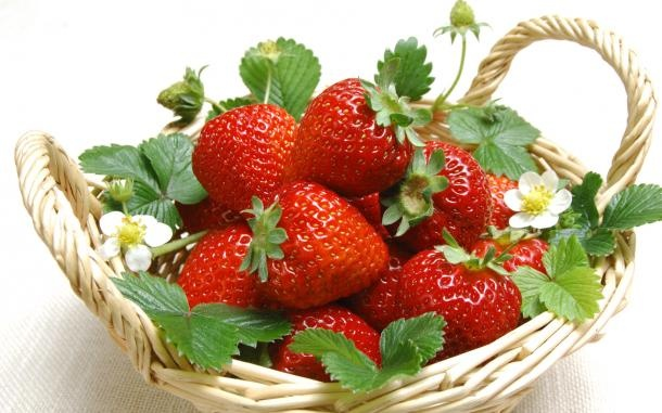 A wooden basket with strawberries, strawberry leaves and white small strawberry flowers on white background.