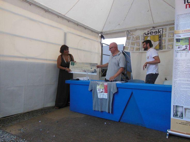 Il momento della consegna dell'Assegno pro-forma ad Ai.Bi. (dott.ssa Dinah Caminiti), durante l'incontro al Geek Party Messina, ieri (2015-07-19) alle 17.00 circa, alla presenza di Giampiero Bronzetti. — a Messina.