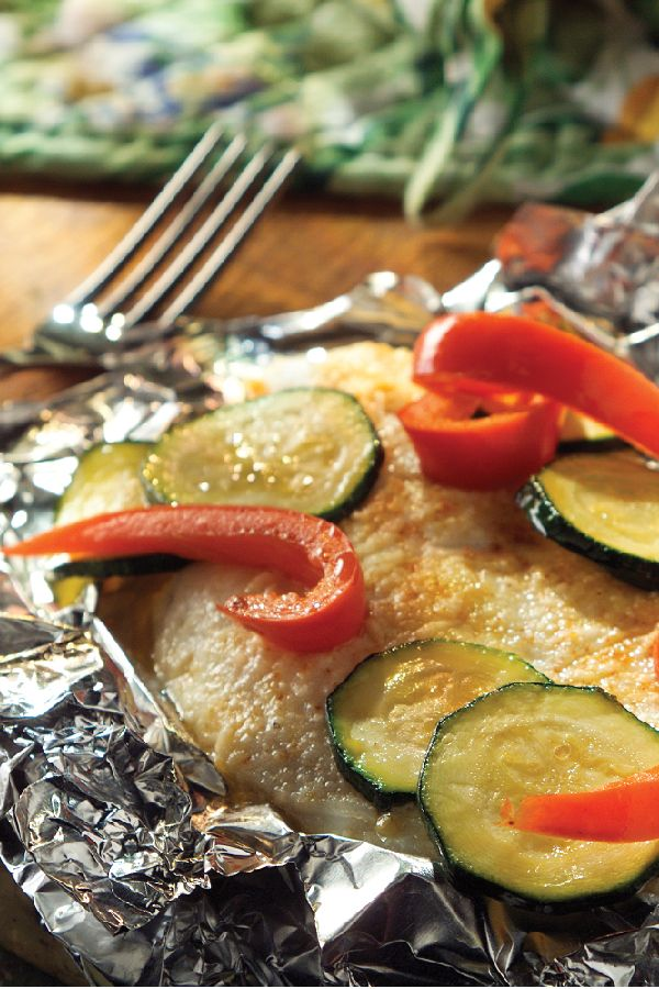 Foil-Wrapped Fish with Creamy Parmesan Sauce – Tender fish fillets are topped with mayonnaise, Parmesan cheese, and crisp vegetables, then wrapped in foil packets for an easy grilling recipe.